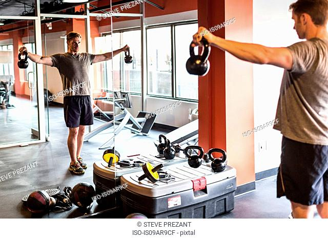 Mid adult man looking at himself in gym mirror training with kettle bells