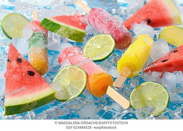 Watermelon, fruit popsicle and lime slices on ice cubes
