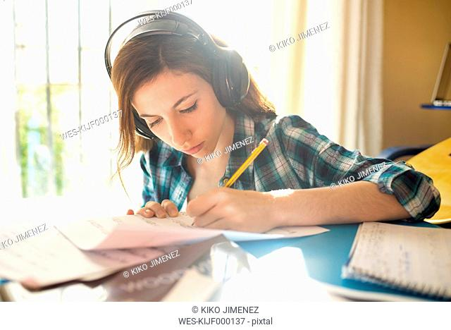 Young woman wearing headphones writing on music sheet