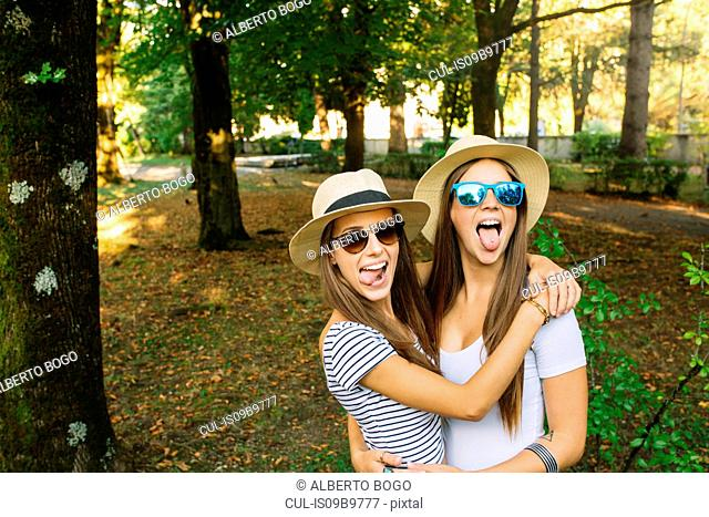 Portrait of two young female friends in trilby hats sticking out tongues in park