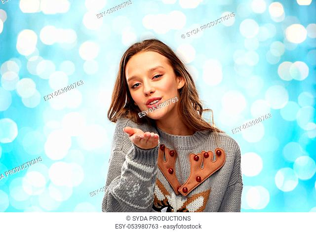 woman in ugly christmas sweater sending air kiss