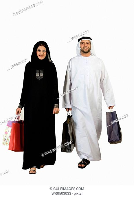 Arab couple with shopping bags, smiling