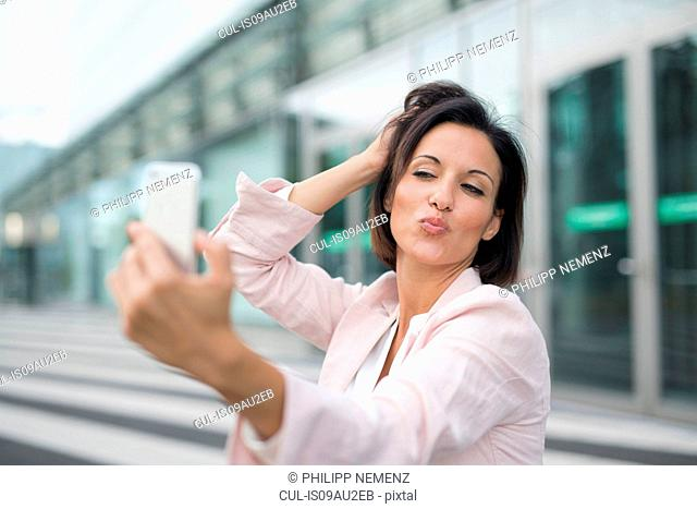 Mature businesswoman puckering for smartphone selfie at airport