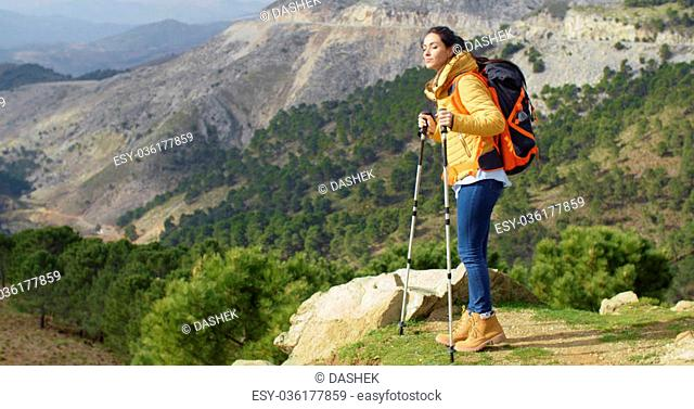 Active fit young woman hiker wearing a backpack pausing to lean on her poles as she enjoys the panoramic mountain view