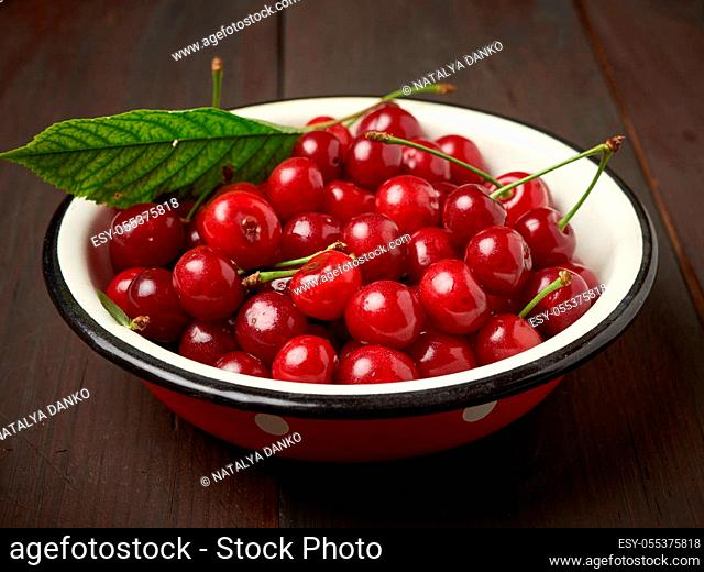ripe red cherry in a round metal bowl on a brown wooden background, close up