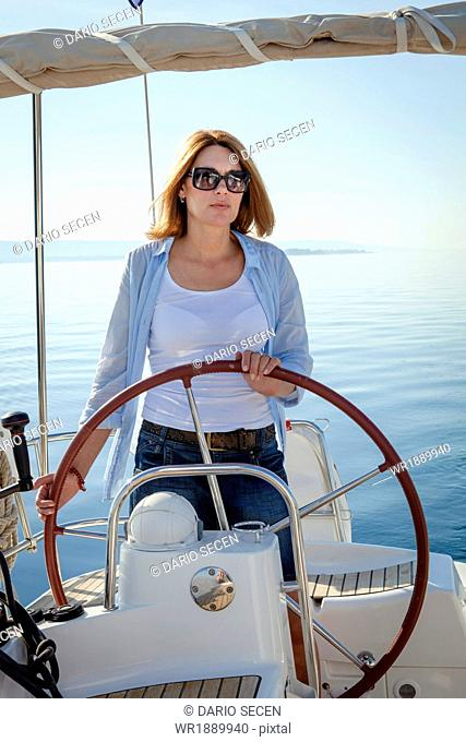 Mature woman on sailboat, steering, Adriatic Sea, Croatia