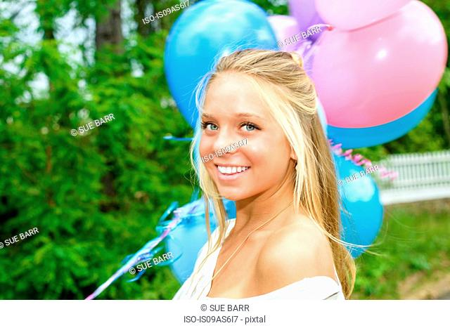 Portrait of pretty young woman with long blond hair holding bunch of balloons