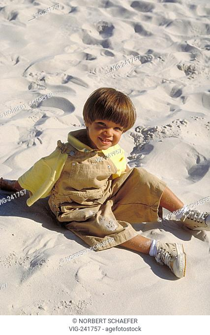 beachscene, full-figure, portrait, 6-year-old boy wearing yellow shirt, beige trousers and gym shoues sits smiling in the sand  - GERMANY, 08/08/2004