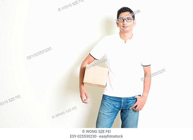 Courier delivery service concept. Indian man holding a brown box, standing on plain background with shadow. Asian handsome guy model