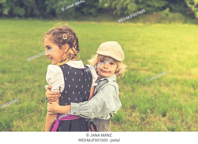Germany, Saxony, little boy holding girl on a meadow