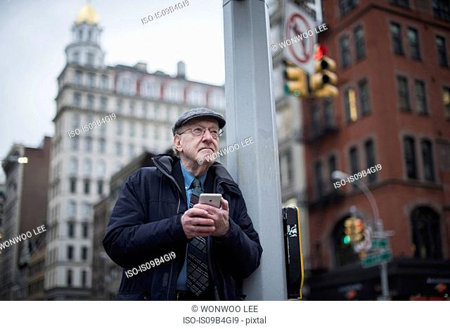Man leaning against lamppost holding smartphone, Manhattan, New York, USA