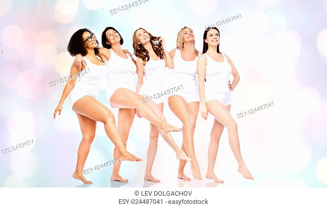 friendship, beauty, body positive and people concept - group of happy women different in white underwear over holidays lights background