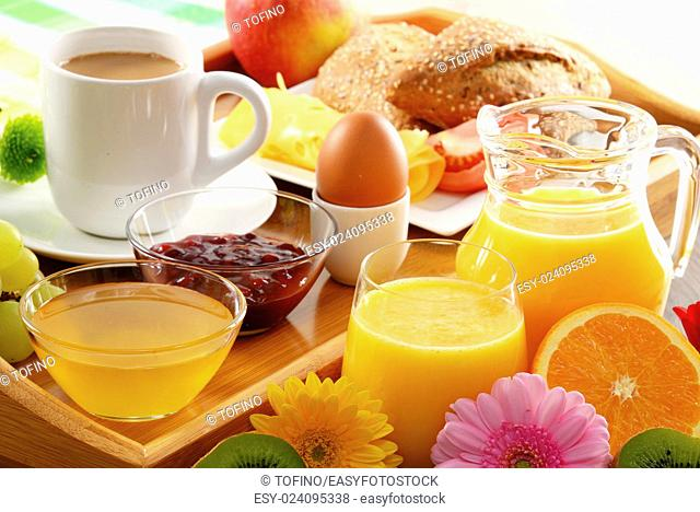 Breakfast on tray served with coffee, orange juice, egg, rolls and honey. Balanced diet