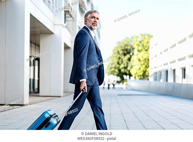 Mature businessman with rolling suitcase on the go in the city