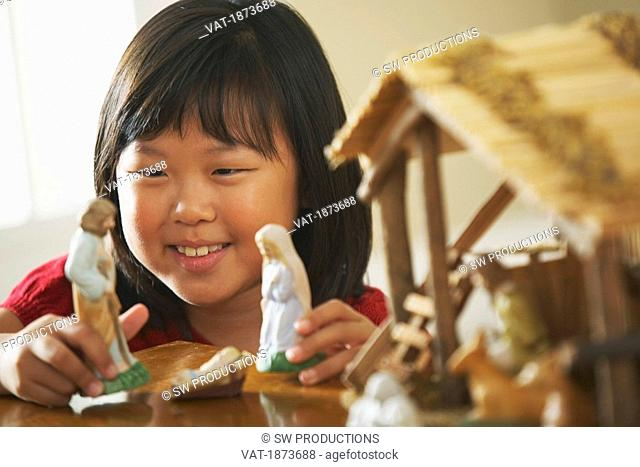 A Girl Plays With Figurines From A Nativity Scene