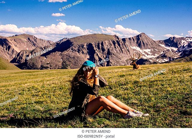 Woman sitting in field with moose, Rocky Mountain National Park, Colorado, USA