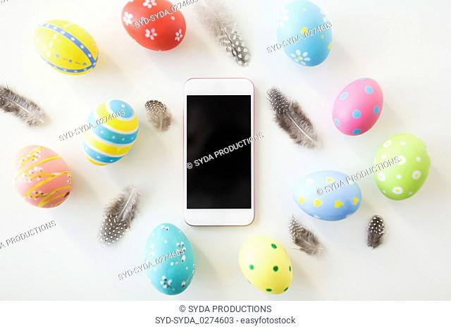 smartphone with easter eggs and quail feathers