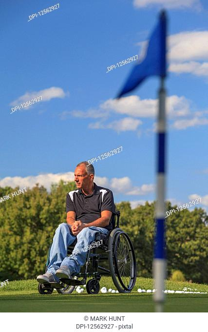 Man with spinal cord injury in a wheelchair waiting to play golf