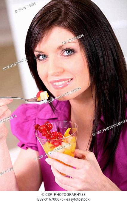 Brunette with a glass of fruit salad