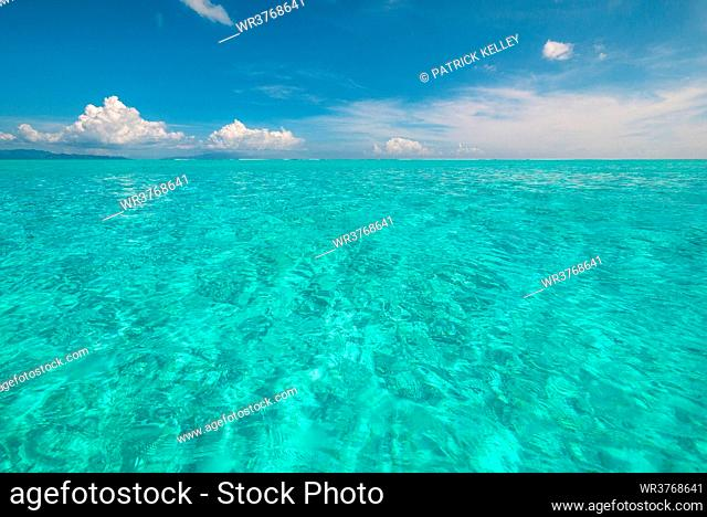 The crystal clear lagoon waters of French Polynesia on a calm sunny day, French Polynesia, South Pacific islands, Pacific