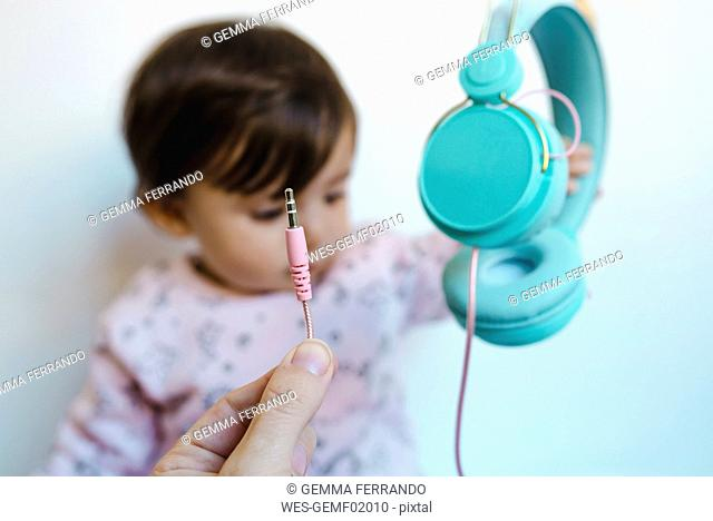 Hand holding plug in front of sad baby girl with headphones, close-up