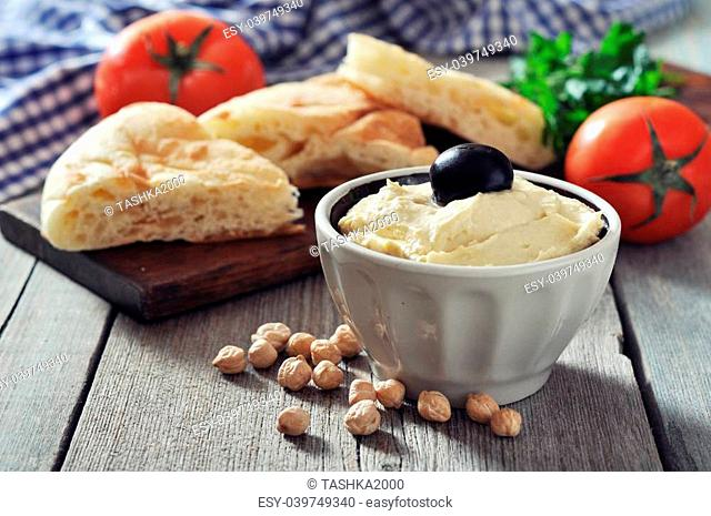 Bowl of fresh hummus with olive and bread slices on wooden background