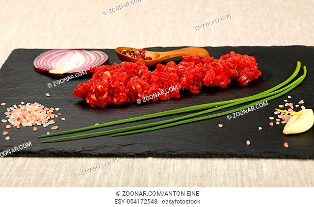 Raw minced beef red meat cutlet, spices, peppercorn in wooden scoop, spring green chive, onion, garlic cloves and Himalayan salt on black slate board, close up