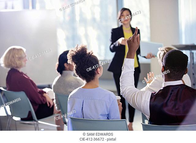 Businesswoman leading conference presentation, answering audience questions