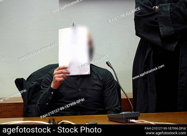 27 January 2021, North Rhine-Westphalia, Cologne: One of the three defendants is sitting in the courtroom at the start of their trial before the Regional Court...