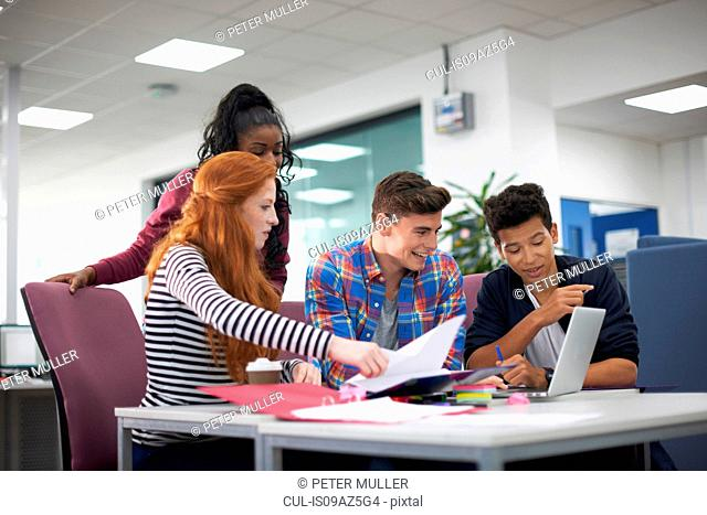 Four young adult college students teamworking at desk