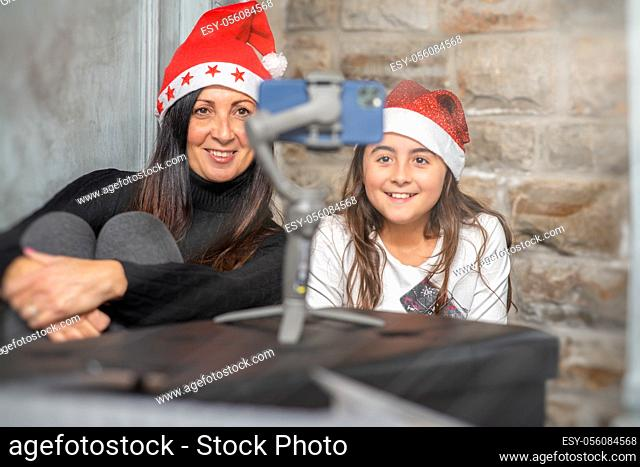 Mother and daughter wearing Santa Red Hat at home in video call with parents