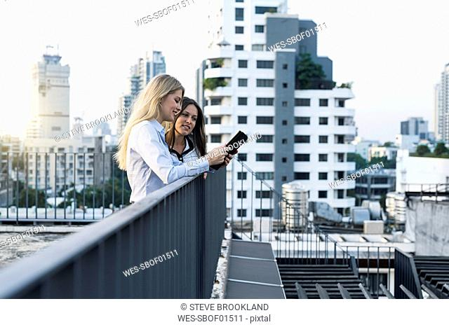 Two businesswomen talking on city rooftop, using digital tablet