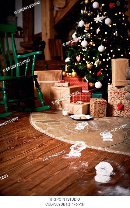 Christmas tree surrounded by presents, Santa's footprints leading towards tree