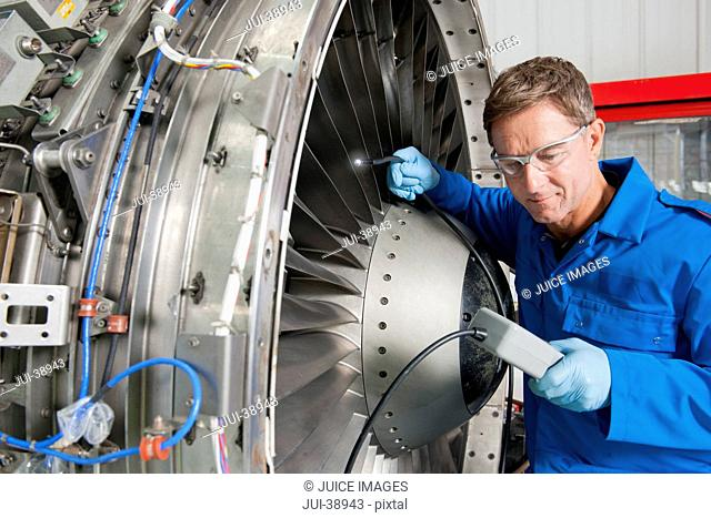 Close up of engineer inspecting engine of passenger jet in hangar