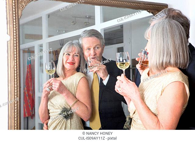 Couple dressed up and having drink in front of mirror