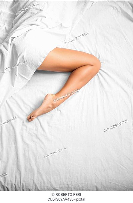 Overhead view of white sheets and female bare leg on bed