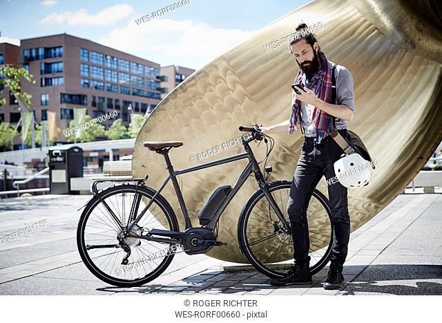Man with electric bicycle looking at his cell phone