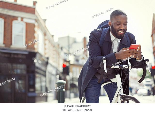 Young businessman commuting with bicycle, texting with cell phone on sunny urban street