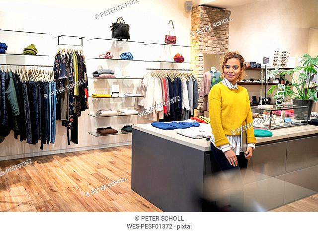 Young woman working in fashion store, using digital tablet