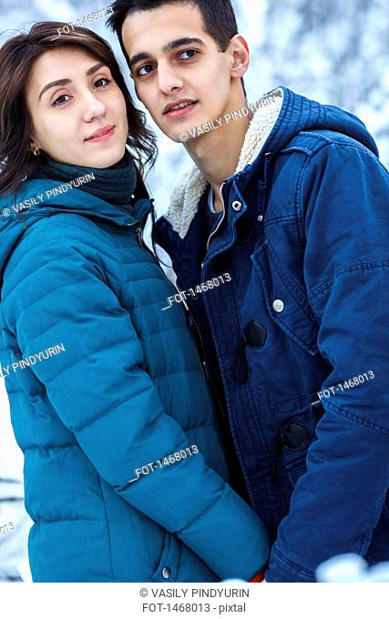 Loving young couple in warm clothing looking away