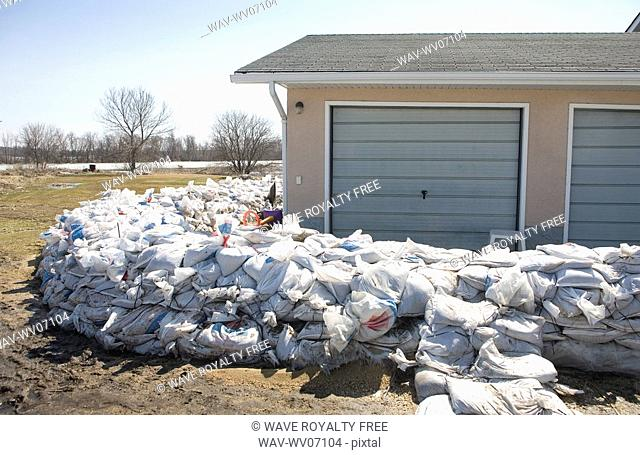 Dyke of sandbags around rural home to protect from Red River floodwaters, rural Manitoba