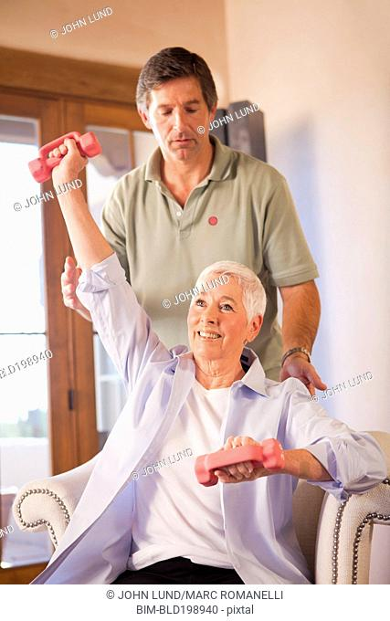 Physical therapist helping woman with exercises