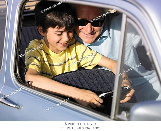 Boy 8-10 and grandfather playing portable video game in backseat of car