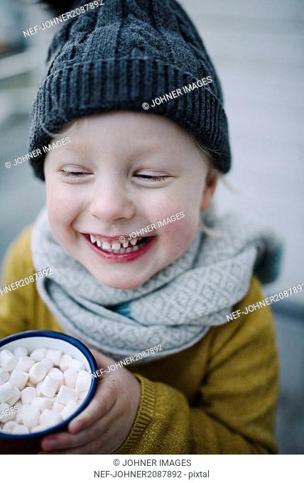 Smiling girl with marshmallow in mug