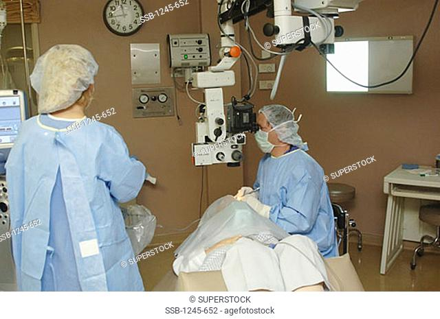 Female surgeon operating on a patient's eye with another female surgeon standing near her