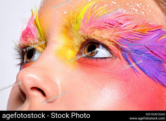 Close-up shot of female face. Woman with bright stylish eyes make-up and false fashion feather eyelashes