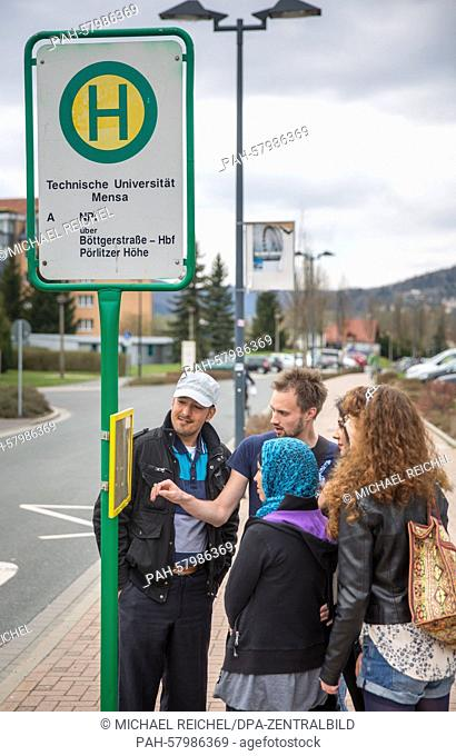 Sponsors Stephanie Reiss(R) and Erik Huebner (2-L) talk with the family members of a refugee named Seyyedali (L) about a bus timetable in Ilmenau, Germany