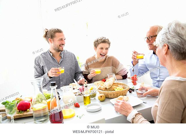 Happy senior couple with adult children having lunch at home