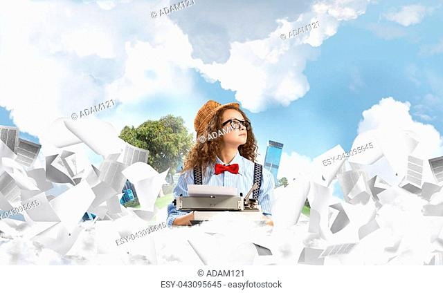 Young woman writer in hat and eyeglasses using typing machine while sitting at the table among flying papers with floating city island and cloudy skyscape on...