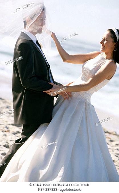 Bride and groom having fun on beach with wedding veil